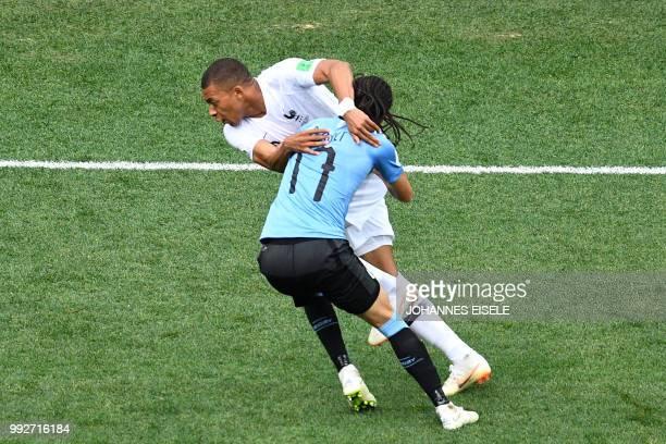 TOPSHOT Uruguay's defender Diego Laxalt vies for the ball with France's forward Kylian Mbappe during the Russia 2018 World Cup quarterfinal football...