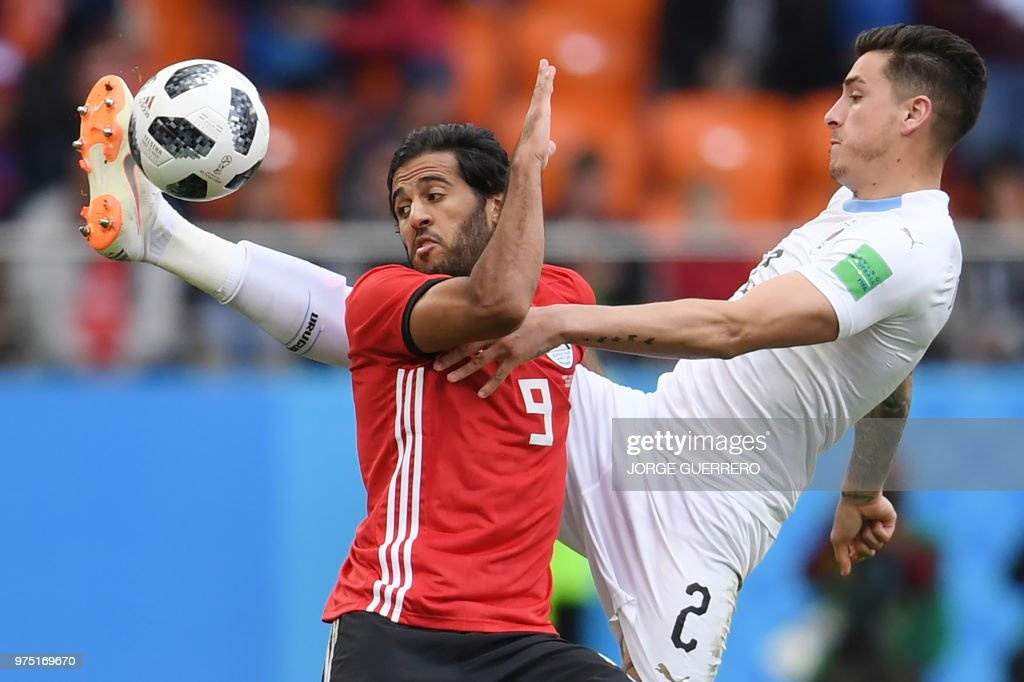 Uruguay's defender Jose Gimenez (R) goes for the ball against Egypt's forward Marwan Mohsen (L) during the Russia 2018 World Cup Group A football match between Egypt and Uruguay at the Ekaterinburg Arena in Ekaterinburg on June 15, 2018. (Photo by JORGE GUERRERO / AFP) / RESTRICTED