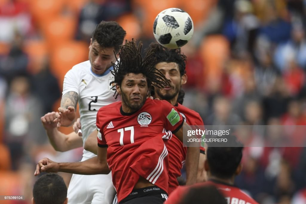 TOPSHOT - Uruguay's defender Jose Gimenez (L) rises above the Egyptian defence to head the ball and score the opening goal during the Russia 2018 World Cup Group A football match between Egypt and Uruguay at the Ekaterinburg Arena in Ekaterinburg on June 15, 2018. (Photo by JORGE GUERRERO / AFP) / RESTRICTED