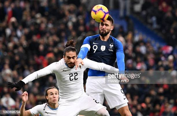TOPSHOT Uruguay's defender Martin Caceres vies with France's forward Olivier Giroud during the friendly football match France vs Uruguay on November...