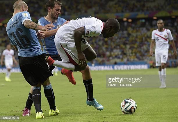 Uruguay's defender Maximiliano Pereira tackles Costa Rica's forward Joel Campbell during a Group D football match between Uruguay and Costa Rica at...
