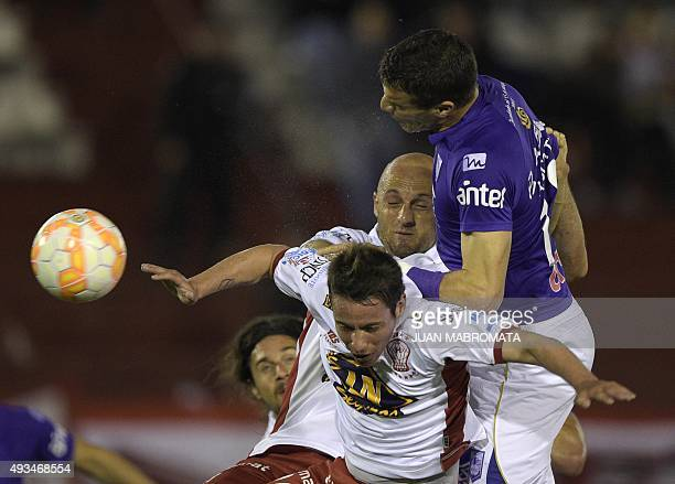 Uruguay's Defensor Sporting's defender Andres Scotti vies for the ball with Argentina's Huracan's midfielder Mauro Bogado and defender Federico...