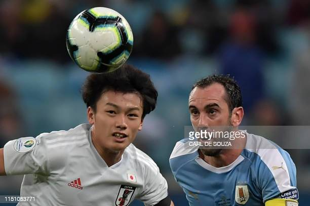 TOPSHOT Uruguay's Diego Godin and Japan's Ayase Ueda eye the ball during the Copa America football tournament Group C match between Uruguay and Japan...