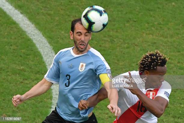 Uruguay's Diego Godin and Peru's Andre Carrillo jump for the ball during their Copa America football tournament quarter-final match at the Fonte Nova...