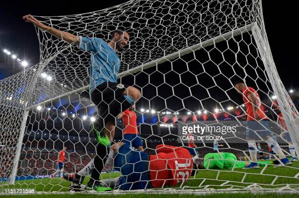 Uruguay's Diego Godin looks at Chile's Gonzalo Jara lying on the back of his goal as Chile's goalkeeper Gabriel Arias also lies on the ground during...
