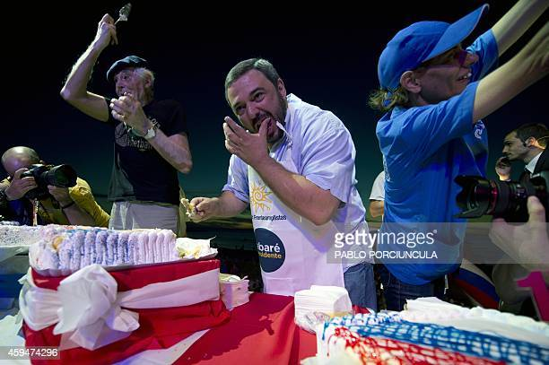 Uruguay's Economy minister Mario Bergara and senator Ernesto Agazzi cut pieces of cake during a campaign rally called by social net for the runoff...