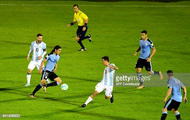 Uruguay's Edinson Cavani is marked by Argentina's Lionel Messi and Paulo Dybala during their 2018 World Cup qualifier football match in Montevideo on...