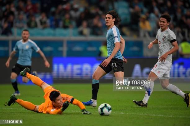 Uruguay's Edinson Cavani shoots at goal as Japan's goalkeeper Eiji Kawashima makes a save during the Copa America football tournament Group C match...