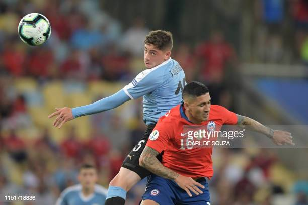 Uruguay's Federico Valverde and Chile's Pedro Pablo Hernandez jump for the ball during their Copa America football tournament group match at Maracana...