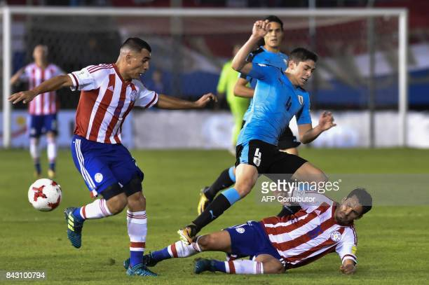 Uruguay's Federico Valverde and Paraguay's Cristian Riveros fall during their 2018 World Cup qualifier football match in Asuncion on September 5 2017...