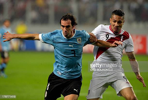 Uruguay's footballer Diego Godin vies with Peru's Paolo Guerrero during their FIFA Brazil 2014 World Cup South American qualifier match in Lima on...