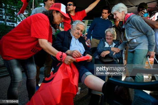 Uruguay's former President and candidate for senator for the Frente Amplio ruling party Jose Mujica autographs a flag next to his wife Uruguay's...