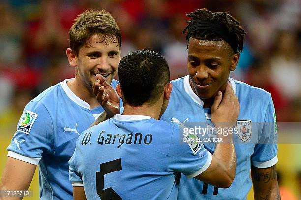 Uruguay's forward Abel Hernandez is congratulated by midfielders Walter Gargano and Gaston Ramirez after scoring against Tahiti during their FIFA...