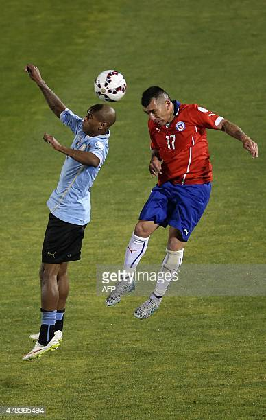 Uruguay's forward Diego Rolan vies for the ball with Chile's defender Gary Medel during their 2015 Copa America football championship quarterfinal...