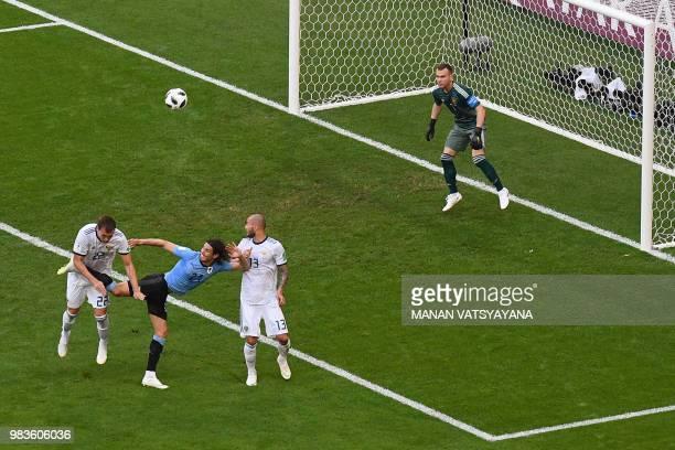 Uruguay's forward Edinson Cavani battles with Russia's forward Artem Dzyuba and Russia's defender Fyodor Kudryashov as Russia's goalkeeper Igor...