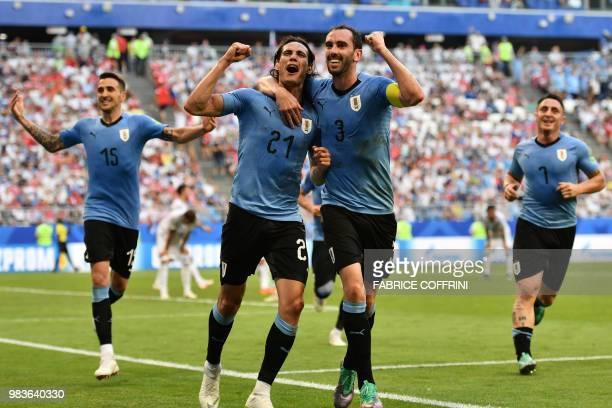TOPSHOT Uruguay's forward Edinson Cavani celebrates with Uruguay's defender Diego Godin Uruguay's midfielder Matias Vecino and Uruguay's midfielder...