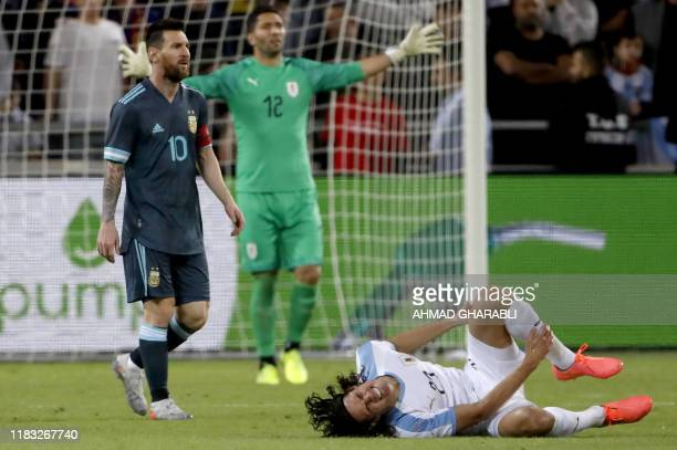Uruguay's forward Edinson Cavani gestures on the ground near Argentina's forward Lionel Messi during the friendly football match between Argentina...