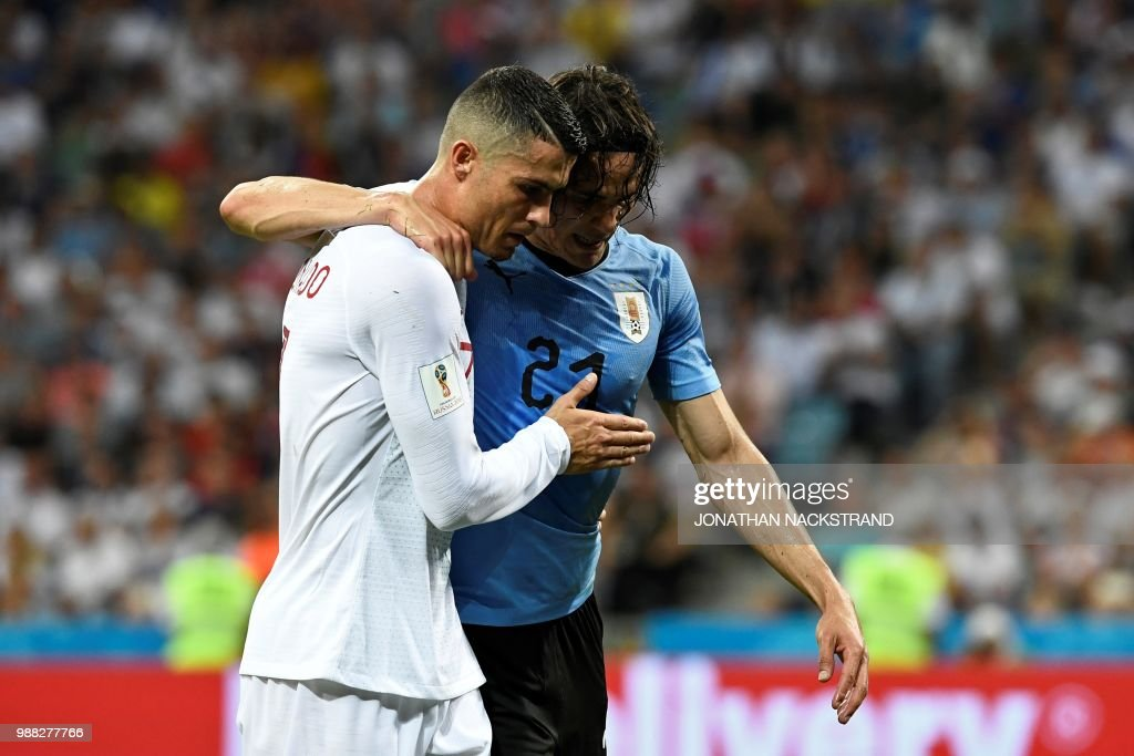 TOPSHOT - Uruguay's forward Edinson Cavani (2ndL) leaves the pitch comforted by Portugal's forward Cristiano Ronaldo during the Russia 2018 World Cup round of 16 football match between Uruguay and Portugal at the Fisht Stadium in Sochi on June 30, 2018. (Photo by Jonathan NACKSTRAND / AFP) / RESTRICTED