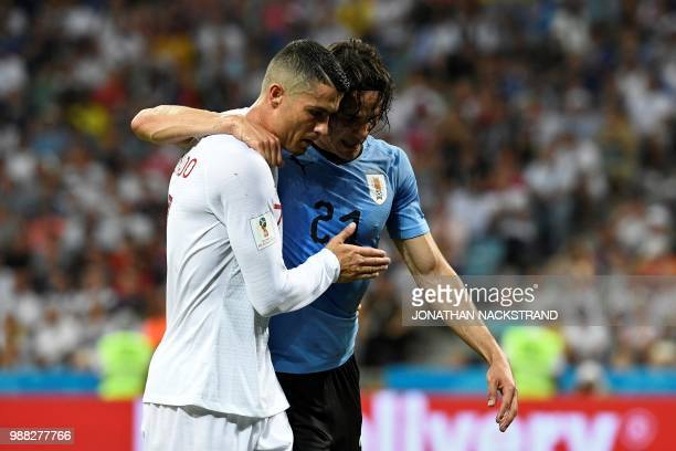 TOPSHOT Uruguay's forward Edinson Cavani leaves the pitch comforted by Portugal's forward Cristiano Ronaldo during the Russia 2018 World Cup round of...