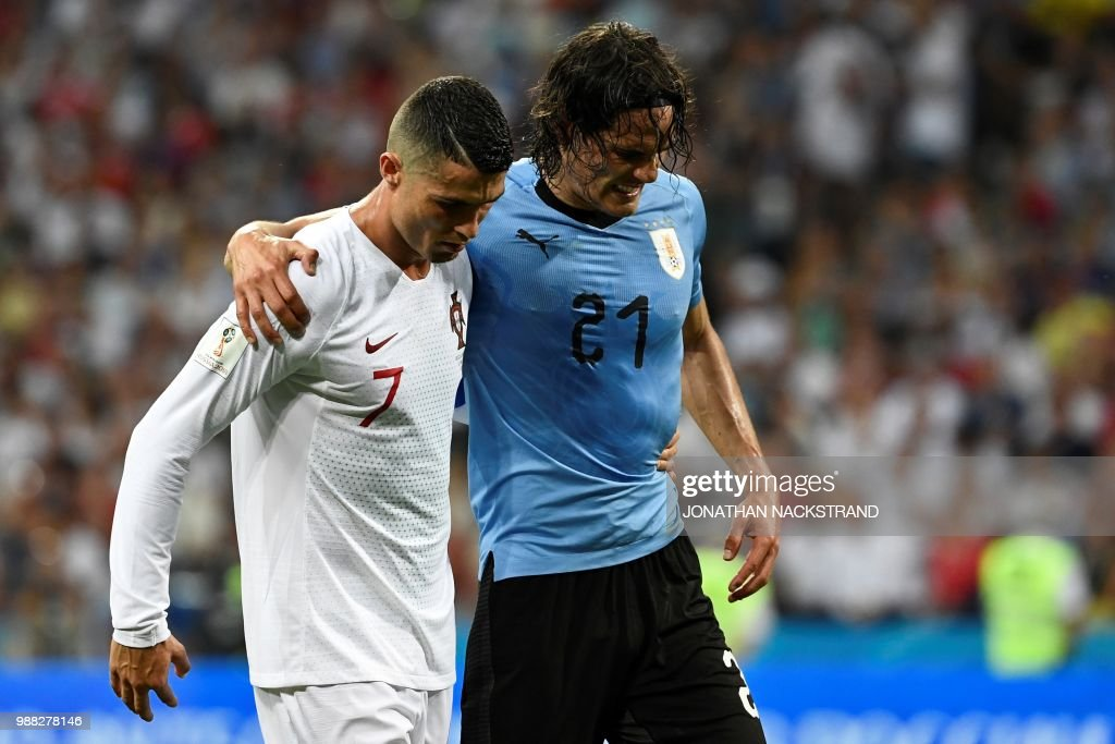 Uruguay's forward Edinson Cavani (2ndL) leaves the pitch comforted by Portugal's forward Cristiano Ronaldo during the Russia 2018 World Cup round of 16 football match between Uruguay and Portugal at the Fisht Stadium in Sochi on June 30, 2018. (Photo by Jonathan NACKSTRAND / AFP) / RESTRICTED