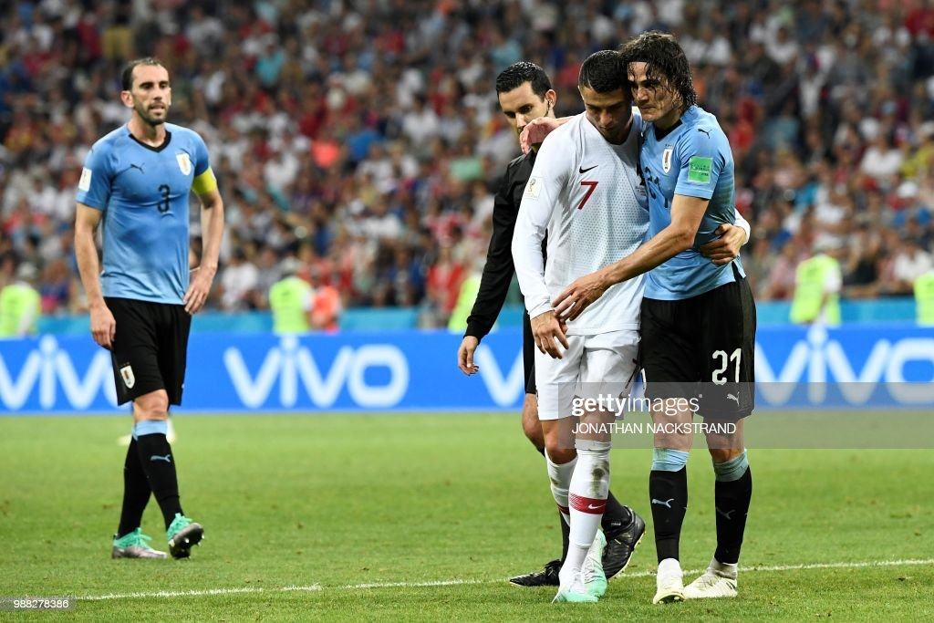 Uruguay's forward Edinson Cavani (r) leaves the pitch comforted by Portugal's forward Cristiano Ronaldo during the Russia 2018 World Cup round of 16 football match between Uruguay and Portugal at the Fisht Stadium in Sochi on June 30, 2018. (Photo by Jonathan NACKSTRAND / AFP) / RESTRICTED