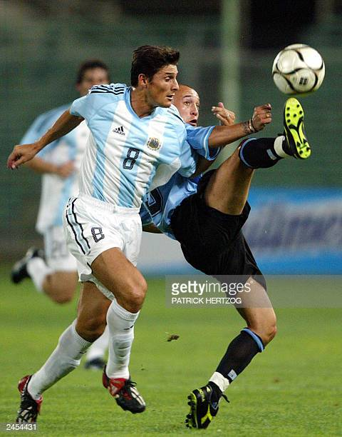 Uruguay's forward Ernesto Chevanton battles for the ball with Argentine's defender Javier Zanetti 20 August 2003 at the Franchi stadium in Florence...
