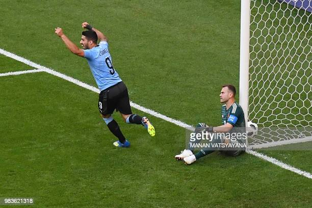 TOPSHOT Uruguay's forward Luis Suarez celebrates and Russia's goalkeeper Igor Akinfeev reacts after Uruguay's second goal scored by Uruguay's...