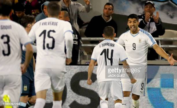 Uruguay's forward Luis Suarez celebrates with teammates after his team scored during the friendly football match between Argentina and Uruguay at the...