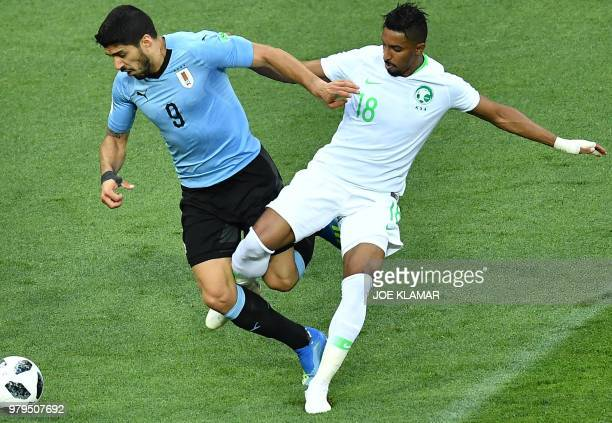 TOPSHOT Uruguay's forward Luis Suarez fights for the ball with Saudi Arabia's forward Salem AlDawsari during the Russia 2018 World Cup Group A...