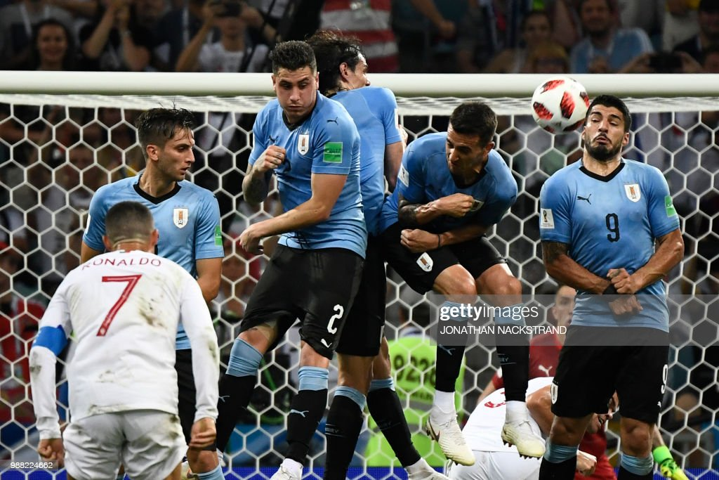 TOPSHOT - Uruguay's forward Luis Suarez (R) jumps to stop a free kick of Portugal's forward Cristiano Ronaldo (front) during the Russia 2018 World Cup round of 16 football match between Uruguay and Portugal at the Fisht Stadium in Sochi on June 30, 2018. (Photo by Jonathan NACKSTRAND / AFP) / RESTRICTED