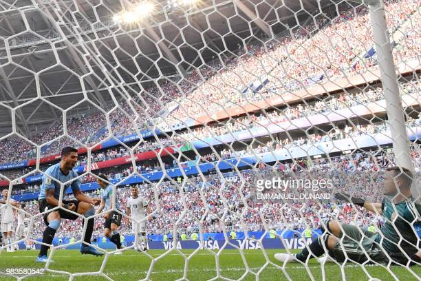 TOPSHOT Uruguay's forward Luis Suarez reacts opposite Russia's goalkeeper Igor Akinfeev after Uruguay's second goal during the Russia 2018 World Cup...