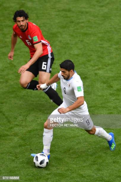 Uruguay's forward Luis Suarez runs the ball shadowed by Egypt's defender Ahmed Hegazi during the Russia 2018 World Cup Group A football match between...