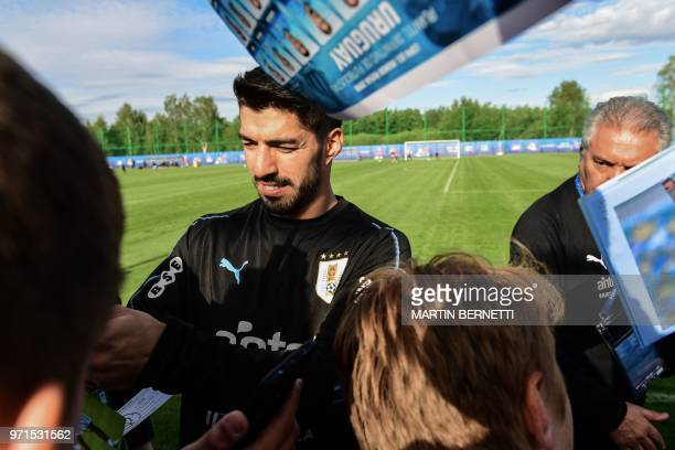 Uruguay's forward Luis Suarez signs autographs after taking part in a training session of Uruguay national football team ahead of the Russia 2018...