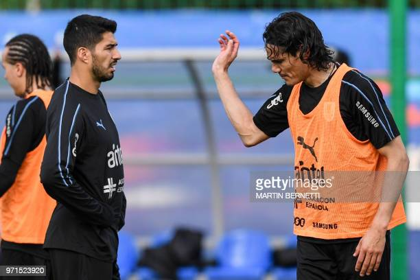 Uruguay's forwards Luis Suarez and Edinson Cavani speak together as they take part in a training session of Uruguay national football team ahead of...