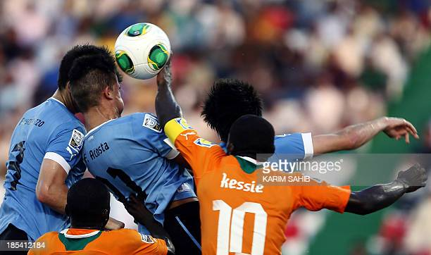 Uruguay's Franco Acosta and Fabrizio Buschiazzo try to head the ball as Cote d'Ivoire's Franck Kessie fouls with a hand ball during their FIFA U17...