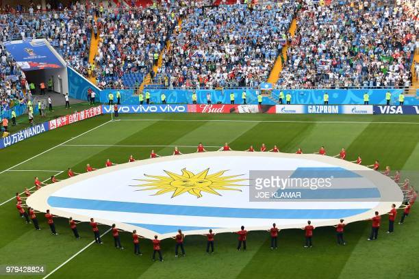 Uruguay's giant flag is seen on the pitch before the start of the Russia 2018 World Cup Group A football match between Uruguay and Saudi Arabia at...