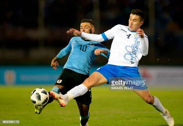 Uruguay's Giorgian De Arrascaeta and Uzbekistan's Akramjon Komilov vie for the ball during the international friendly football match between Uruguay...