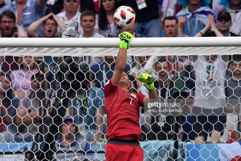 TOPSHOT - Uruguay's goalkeeper Fernando Muslera grabs the crossbar as the ball passes above it during the Russia 2018 World Cup quarter-final football match between Uruguay and France at the Nizhny Novgorod Stadium in Nizhny Novgorod on July 6, 2018.