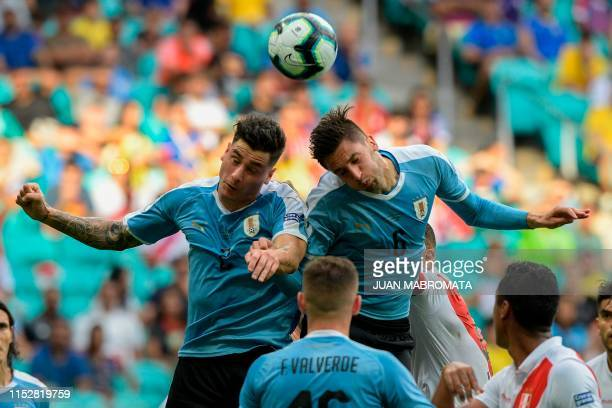 Uruguay's Jose Maria Gimenez and Rodrigo Bentancur jump for a header during their Copa America football tournament quarter-final match against Peru...