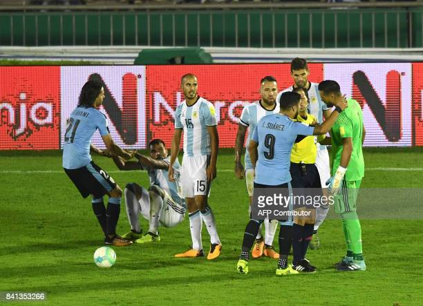 Uruguay's Luis Suarez and Argentina's goalkeeper Sergio Romero talk with Peruvian referee Victor Carrillo during their 2018 World Cup qualifier...