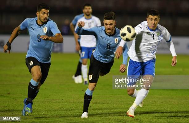 Uruguay's Luis Suarez and Nahitan Nandez vie for the ball with Uzbekistan's Akramjon Komilov during their international friendly football match...