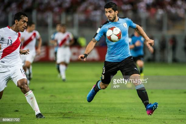TOPSHOT Uruguay's Luis Suarez and Peru's midfielder Renato Tapia vie for the ball during the 2018 FIFA World Cup qualifier football match in Lima on...