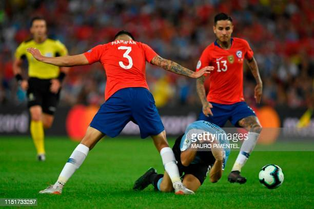 Uruguay's Luis Suarez gestures on the ground between Chile's Guillermo Maripan and Erick Pulgar during their Copa America football tournament group...