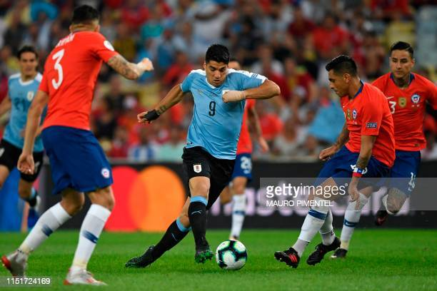 TOPSHOT Uruguay's Luis Suarez is marked by Chile's Gonzalo Jara during their Copa America football tournament group match at Maracana Stadium in Rio...