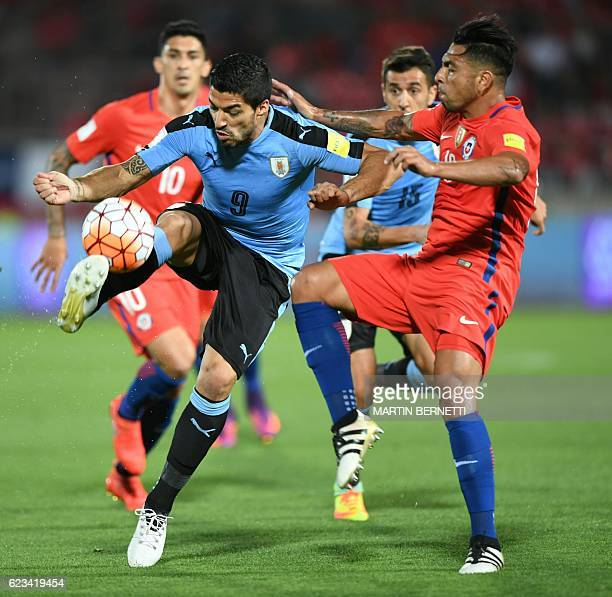TOPSHOT Uruguay's Luis Suarez is marked by Chile's Gonzalo Jara during their 2018 FIFA World Cup qualifier football match in Santiago on November 15...