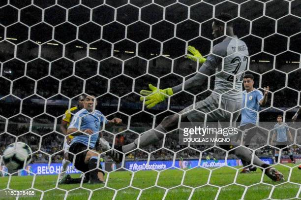 Uruguay's Luis Suarez scores past Ecuador's goalkeeper Alexander Dominguez during their Copa America football tournament group match at the Mineirao...