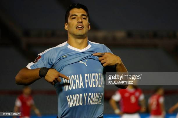 """Uruguay's Luis Suarez shows a t-shirt reading """"Stay Strong Nando and Family"""" after scoring a penalty against Chile during their 2022 FIFA World Cup..."""