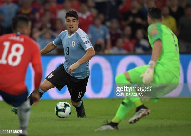 Uruguay's Luis Suarez tries to score past Chile's Gonzalo Jara and goalkeeper Gabriel Arias during their Copa America football tournament group match...