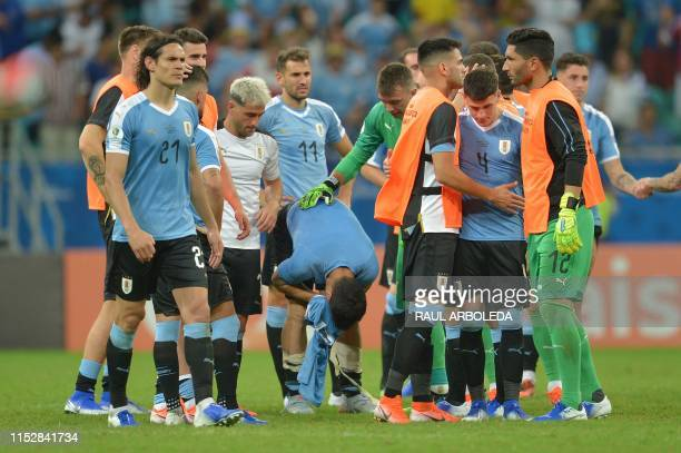 Uruguay's Luis Suarez whose penalty was stopped by Peru's goalkeeper Pedro Gallese and teammates show their dejection after losing in the penalty...