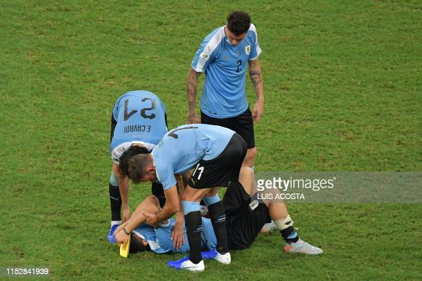 Uruguay's Luis Suarez -whose penalty was stopped by Peru's goalkeeper Pedro Gallese- is comforted by teammates Edinson Cavani , Cristhian Stuani and...